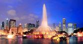 Panorama sullo skyline di Chicago con grattacieli e buckingham fontana nel parco del grant di notte illuminata da luci colorate