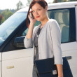 thumbnail of Elegant businesswoman stand by luxury car calling