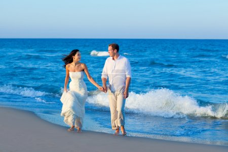 Mediterranean couple walking in blue beach
