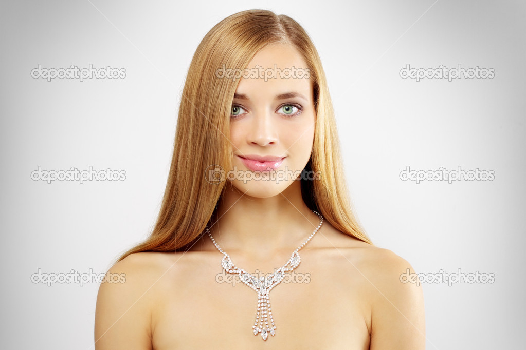 Woman with beautiful necklace on a gray background