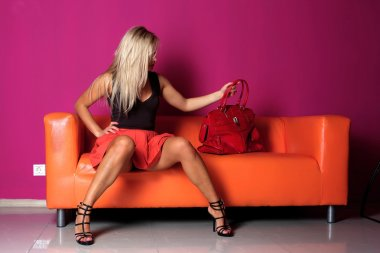 Woman seated on a sofa with red bag