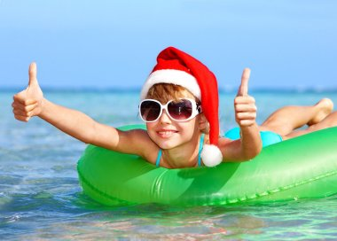 Child in santa hat floating on inflatable ring in sea.