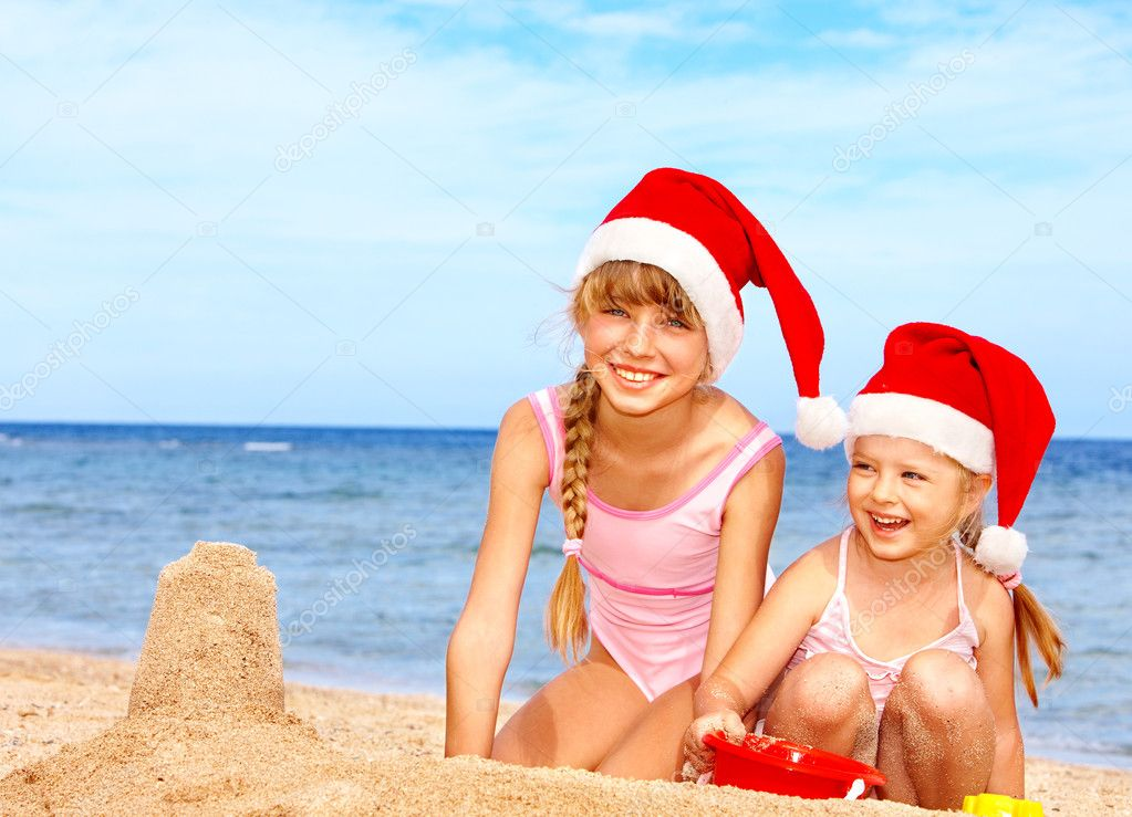 Children in santa hat playing on beach.