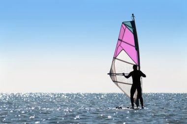 Silhouette of a woman windsurfer