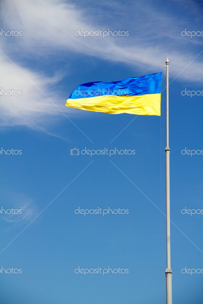 Flag of Ukraine with flag pole waving in the wind on front of bl