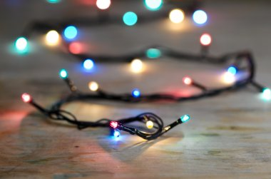Decorative lights of garland on table with blurred background. Shallow DoF stock vector