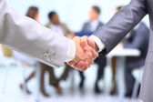 Two successful businessman shaking hands in front of corporate team at offi
