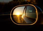 západ slunce v zrcátku automobilu jako závody po silnici