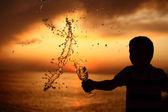 Silueta chlapce vystřikuje z pít ze skla na moře slunce