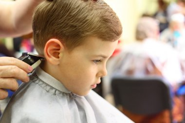 Boy cut in hairdresser's machine