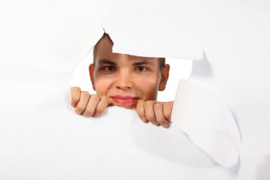 Young man looking out in hole in paper