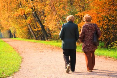 Two elderly women in park in autumn