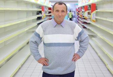 Elderly man stands between empty shelves in shop