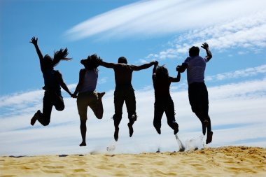 Group of friends jumps on sand, rear view