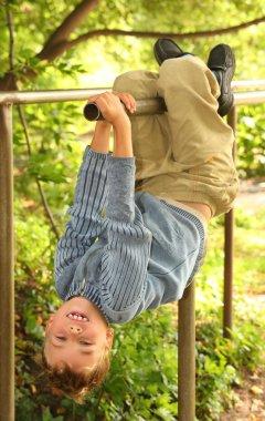 Boy hangs on bars headfirst