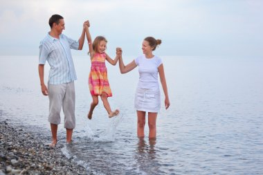 Happy family with little girl on beach in evening, parents lift