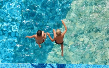 Two children jump in water, top view