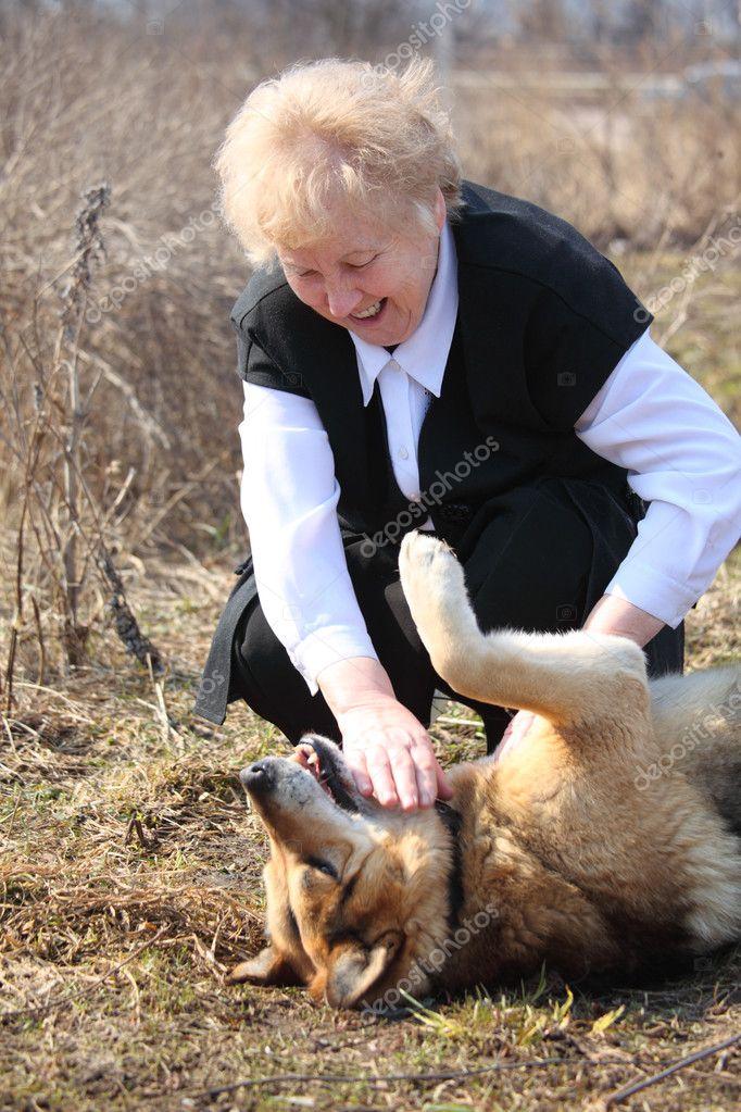 Elderly woman caresses dog