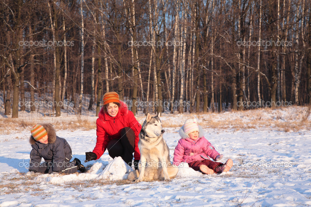 Mother with children and dog in wood in winter
