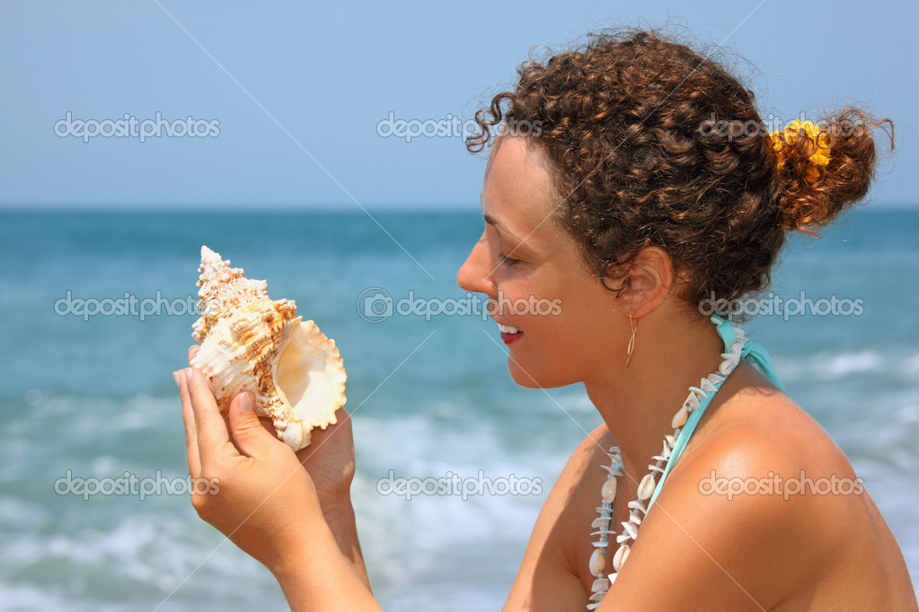 Beautiful woman considering seashell on seacoast