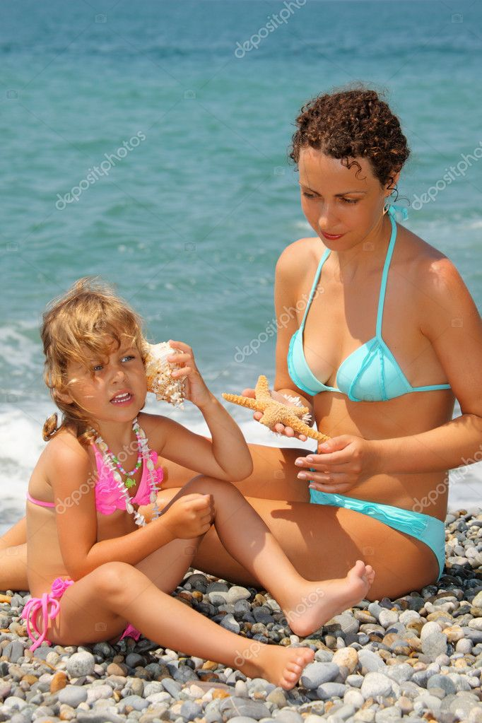 Beautiful woman with pretty little girl has leant seashell bowl