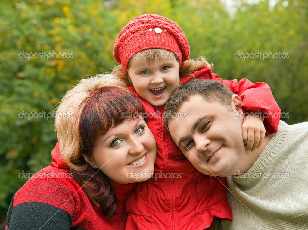 Married couple and little girl in park in autumn