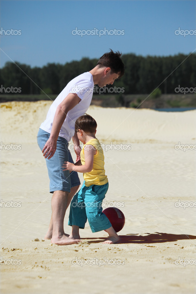 Father with son play football on sand