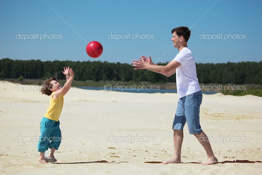 Son throws ball to father on sand