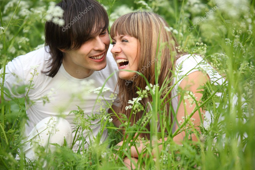 Laughing young pair sits in grass