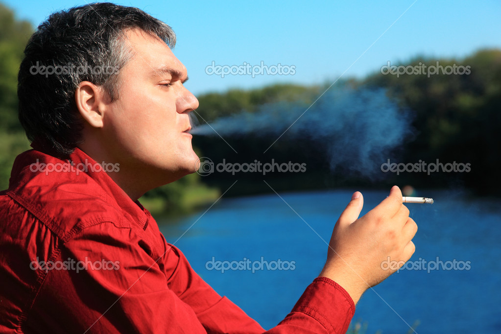 Smoking man on river bank