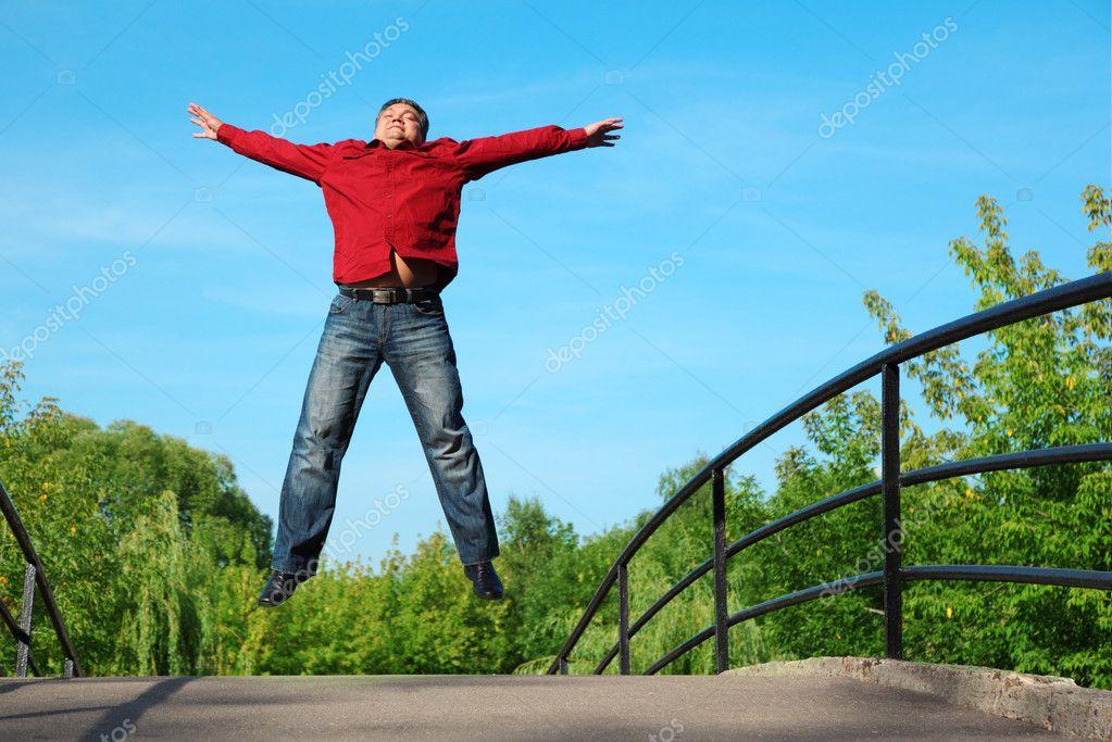 Man in red shirt jumps outdoor in summer on bridge