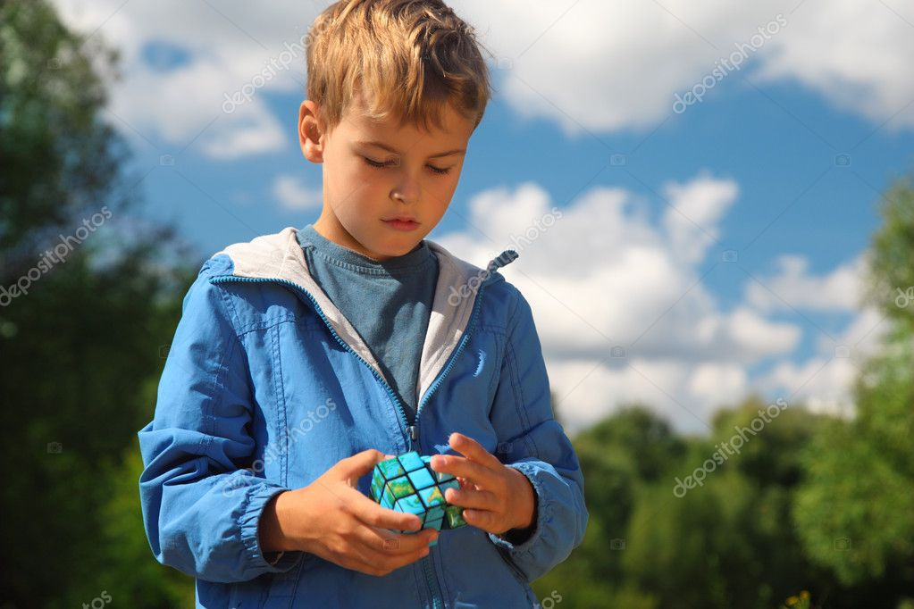 Boy with magic cube outdoor in summer