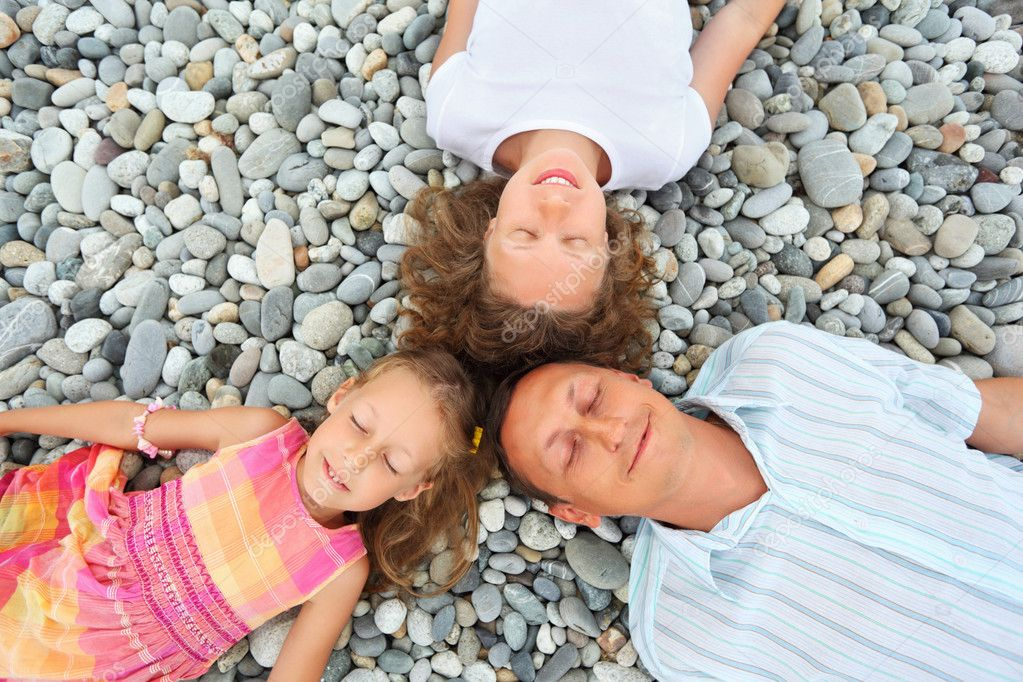 Happy family with little girl lying on stony beach, closed eyes,