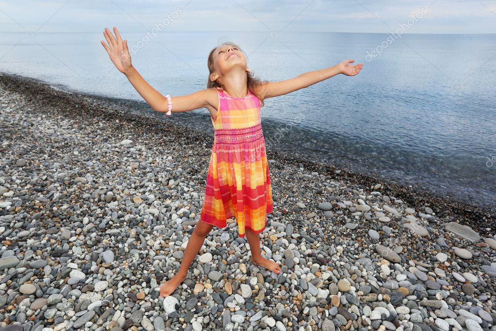 Little girl lifted hands upwards on stony beach