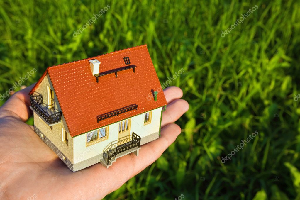 House with garage on palm on background of the herb