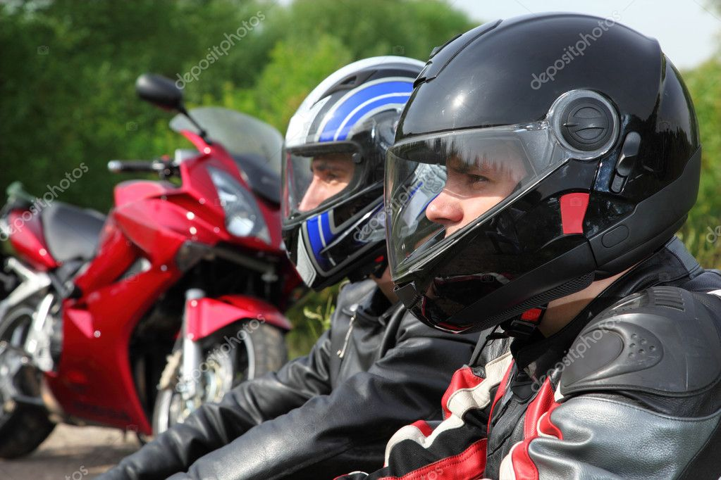 Closeup of two motorcyclists sitting on country road near bikes