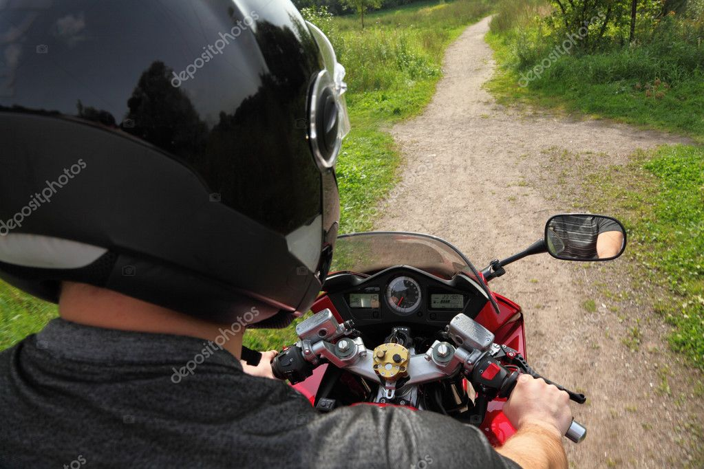 Motorcyclist on country road, view because of shoulder