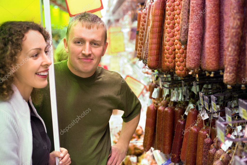 Smiling young man and woman buy sausage in supermarket
