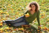 žena s žluté listy leží na trávě