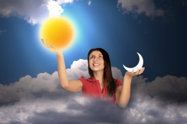Woman in sky with clouds holds moon and sun in hands, collage