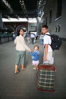 Happy family with little girl at railway station