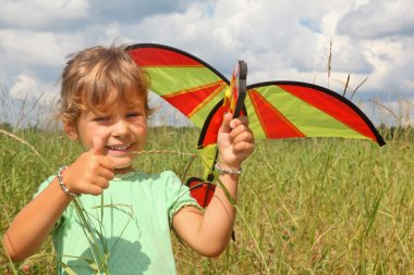 Little girl plays kite on meadow with ok gesture