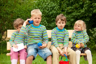 Two boys and two girls on a bench in park. In identical stripe c