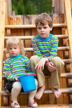 The brother and sister on a children's playground in identical c