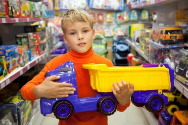 The boy in shop with toy truck in hands