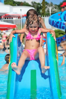 Pretty little girl goes down on hill in aquapark of an entertain