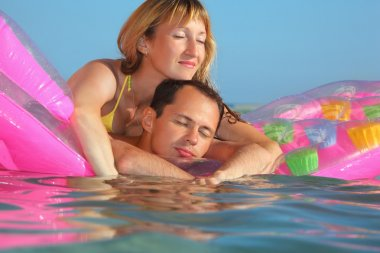 Young man and nice women sleep on an Inflatable mattress in pool
