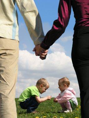 Children sitting on grass and mother with father holding hands c