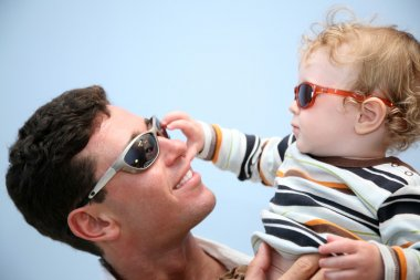 Father with the child in the sunglasses against the background of the sky
