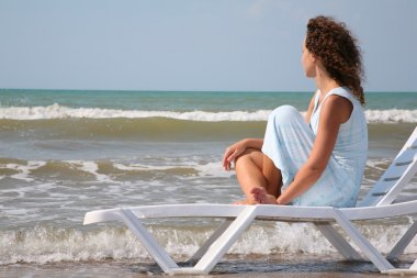Young woman sits in the chaise lounge on the edge of the sea